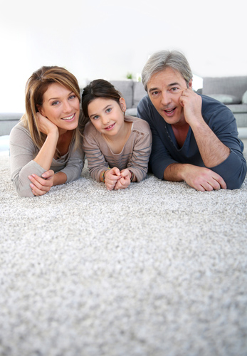 Middle-aged couple with little girl laying on carpet